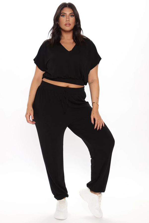 A plus-size model wearing a black lounge set.