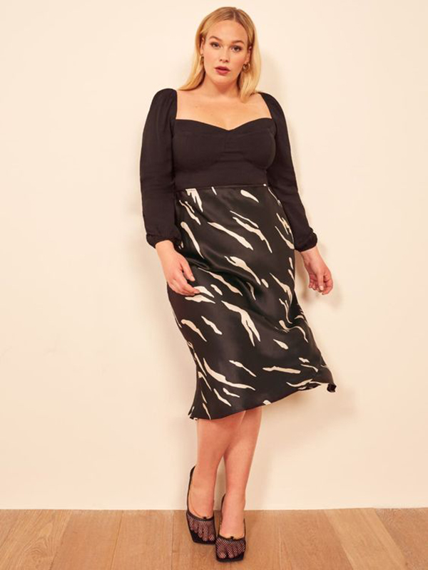 A plus-size model wearing a printed satin midi skirt.