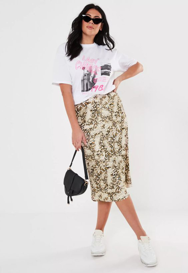 A plus-size model wearing a printed midi skirt.
