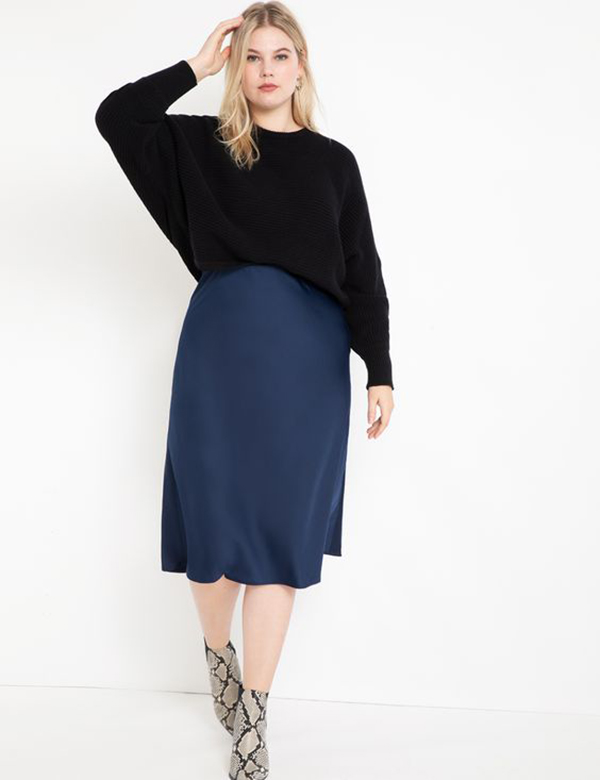 A plus-size model wearing a navy satin midi skirt.