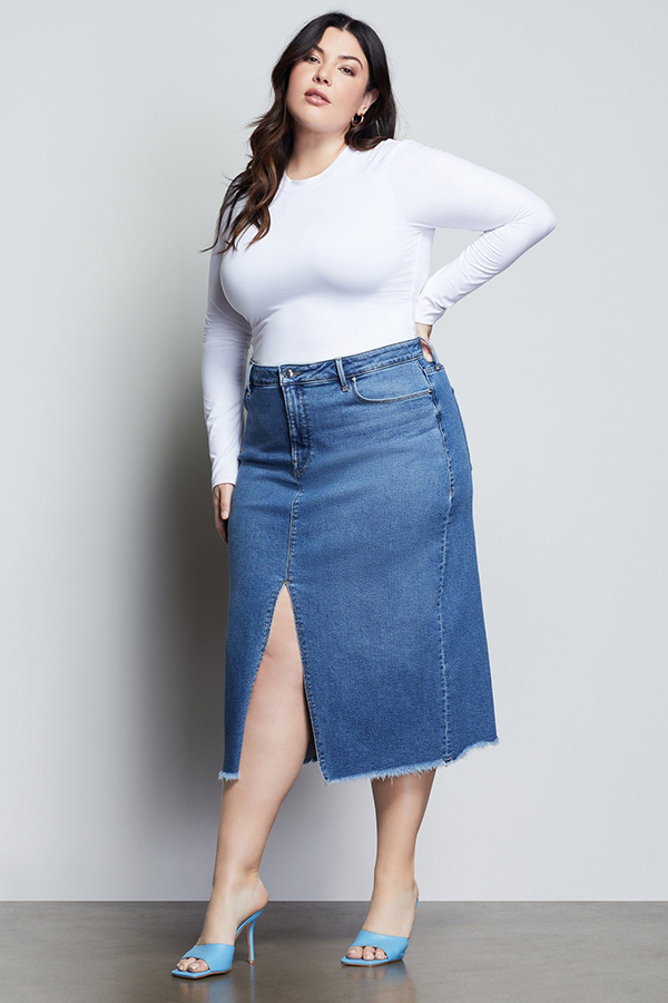 A plus-size model wearing a denim midi skirt.