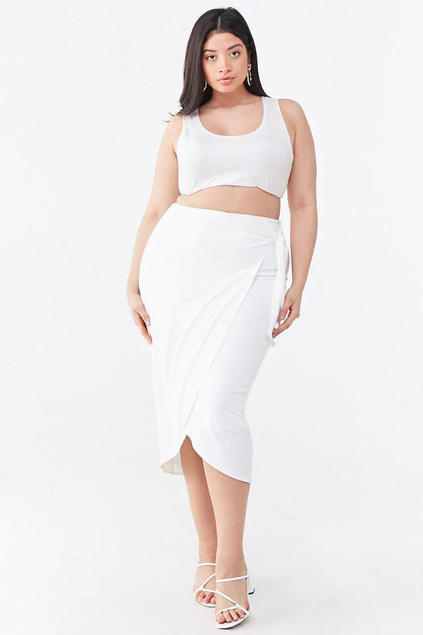 A plus-size model wearing a white wrap midi skirt.