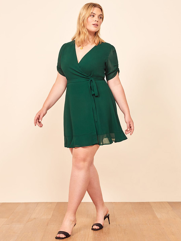 A plus-size model wearing an emerald green mini dress.
