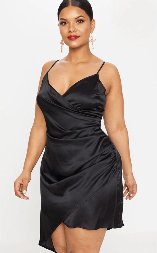 A plus-size model wearing a black satin mini dress.