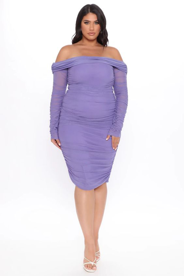 A plus-size model wearing a purple ruched midi dress.
