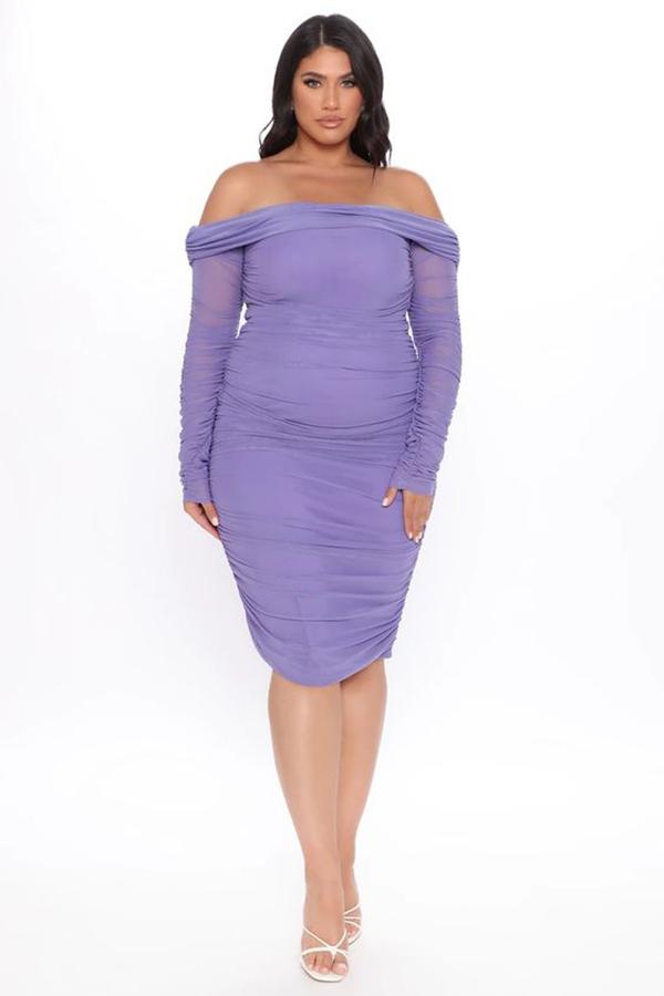 A plus-size model wearing a purple ruched midi dress.