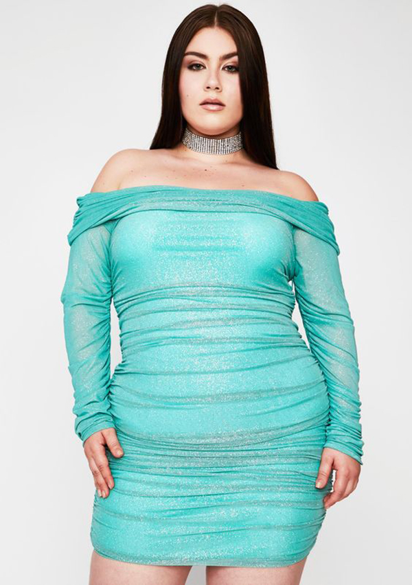 A plus-size model wearing a teal ruched mini dress.