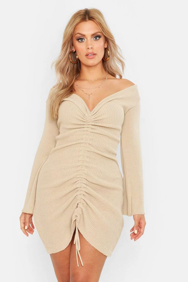 A plus-size model wearing a ruched dress.