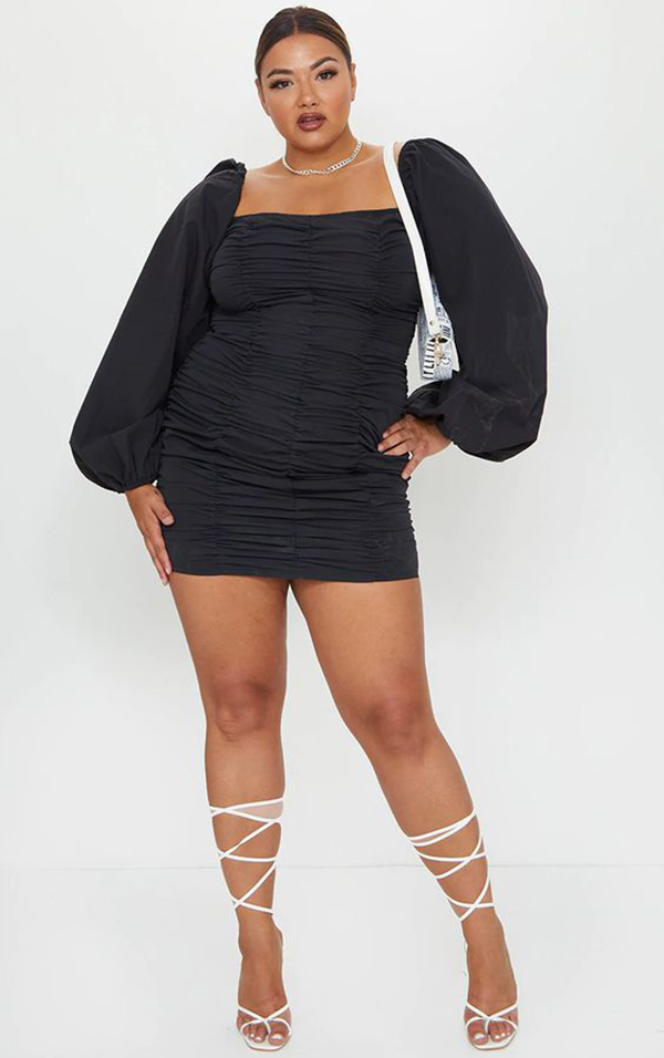A plus-size model wearing a black ruched mini dress.