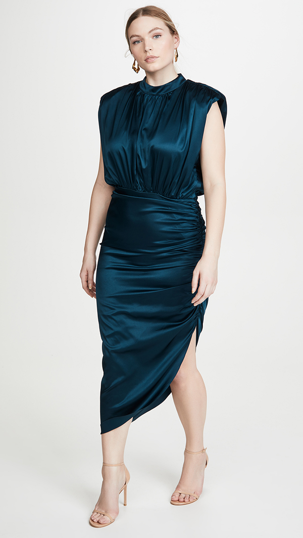 A plus-size model wearing a dark teal ruched midi dress.