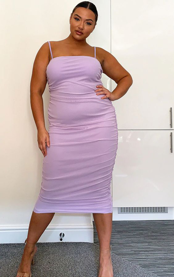 A plus-size model wearing a lavender ruched midi dress.