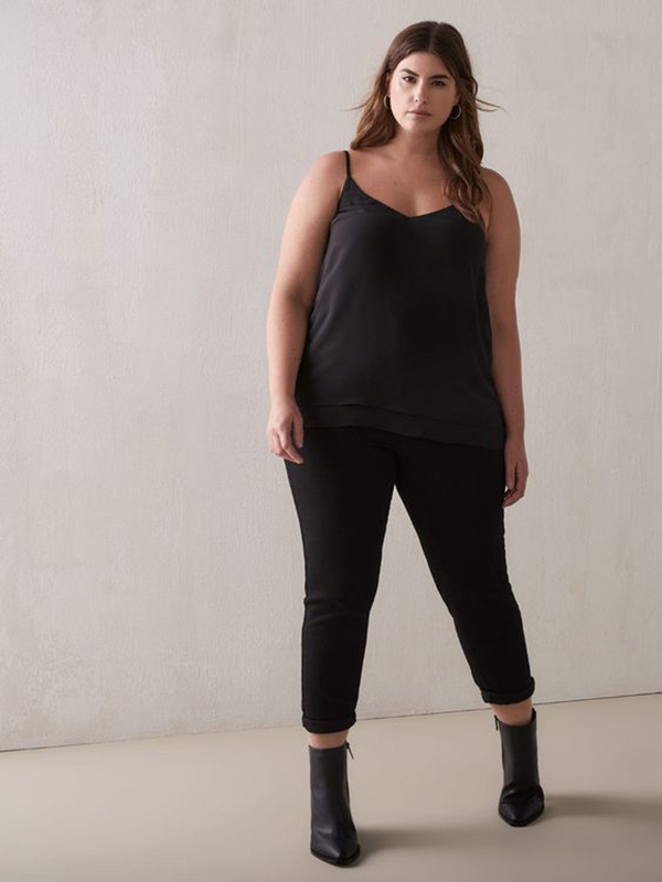 A plus-size model wearing a black satin cami.