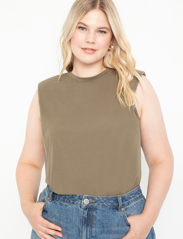A plus-size model wearing an olive shoulder pad tee.