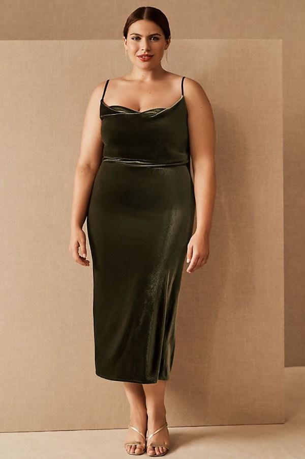 A plus-size model wearing an olive green velvet slip dress.