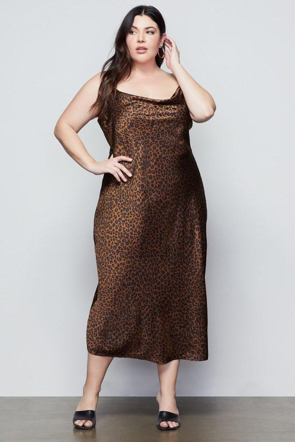 A plus-size model wearing a dark leopard print slip dress.