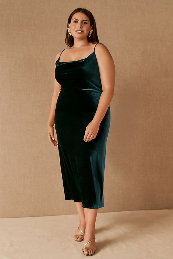 A plus-size model wearing a dark green velvet slip dress.