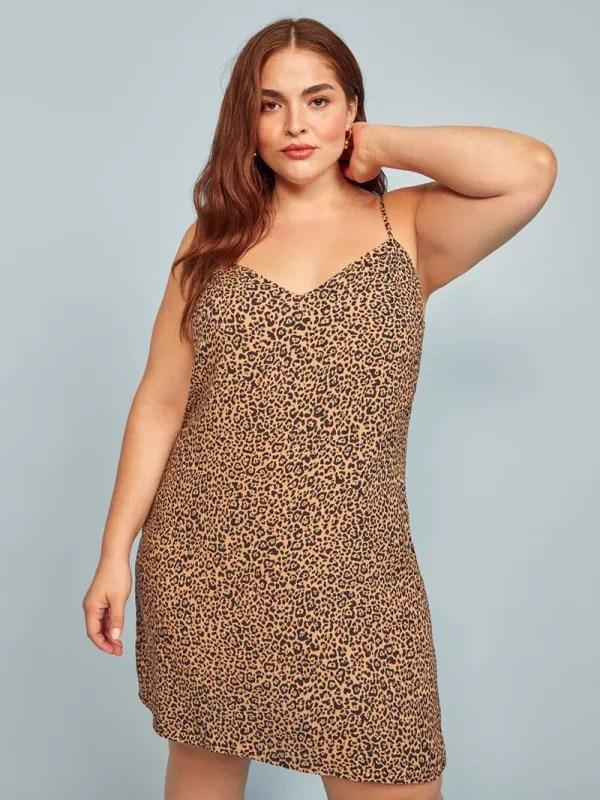 A plus-size model wearing a cheetah print mini slip dress.