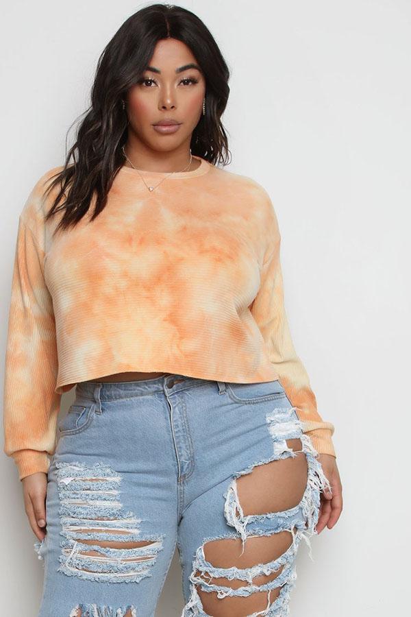 A plus-size model wearing an orange tie-dye top.