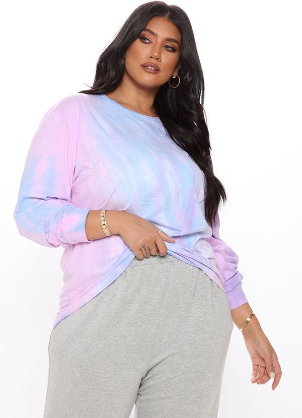 A plus-size model wearing a pink and blue tie-dye sweatshirt.