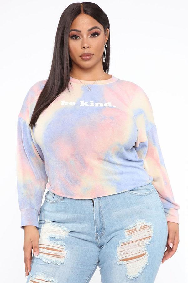 A plus-size model wearing a pastel tie-dye sweatshirt.