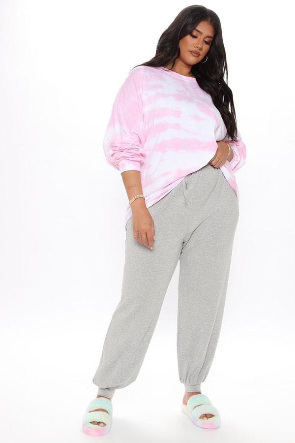 A plus-size model wearing a pink tie-dye sweatshirt.