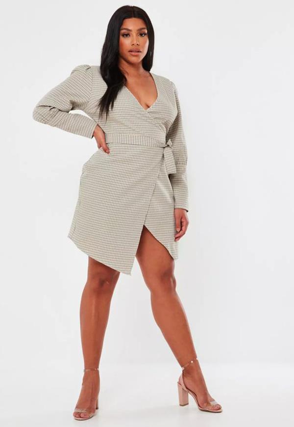 A plus-side model wearing a tailored wrap dress.