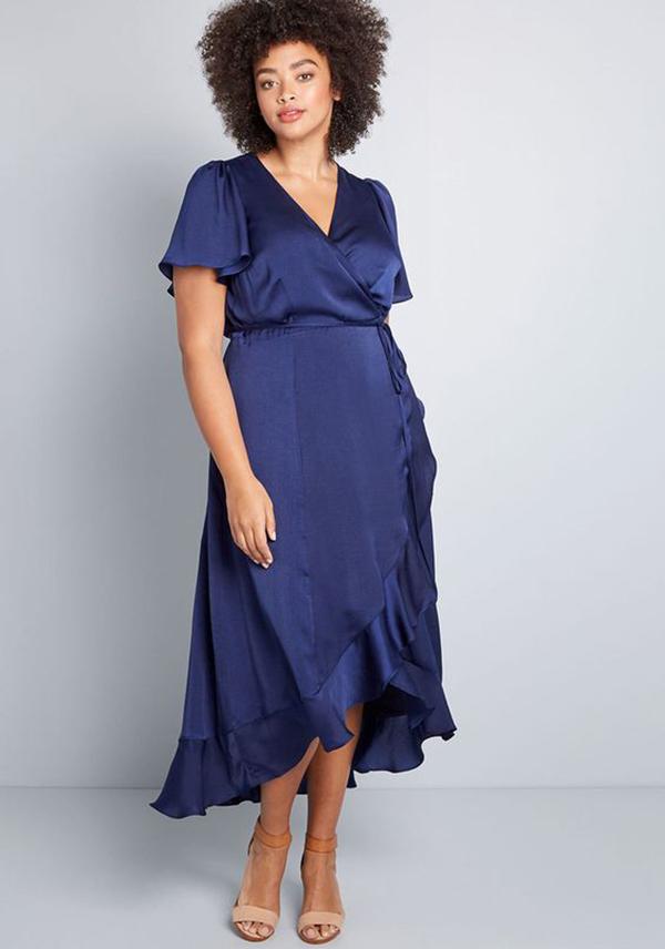 A plus-side model wearing a navy satin wrap dress.