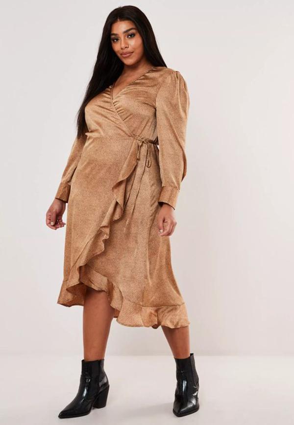 A plus-side model wearing a gold satin wrap dress.