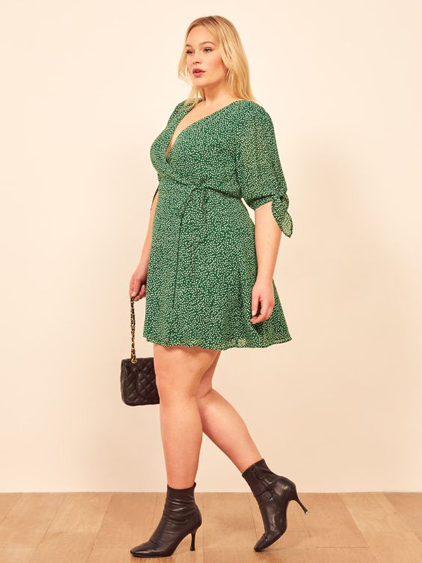 A plus-side model wearing a green polka dot wrap dress.