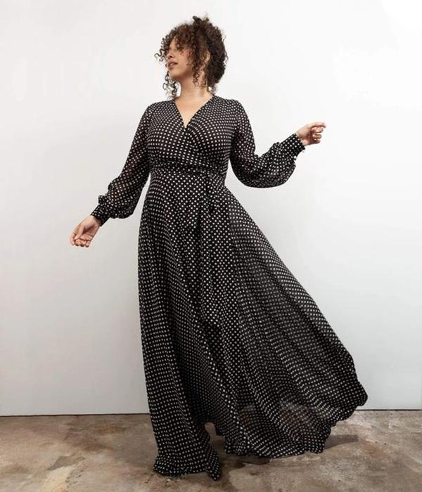 A plus-side model wearing a polka dot wrap maxi dress.