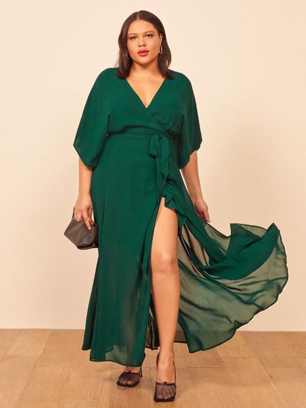 A plus-side model wearing an emerald green wrap maxi dress.