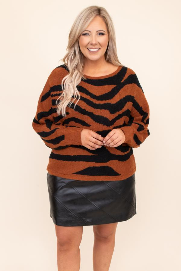 A plus-size model wearing a zebra print sweater.