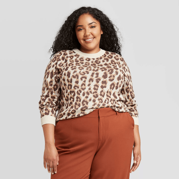 A plus-size model wearing a leopard print sweater.