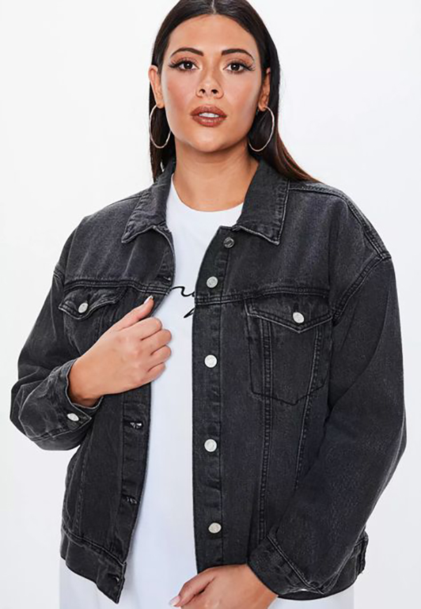 A plus-size model wearing a black denim jacket.