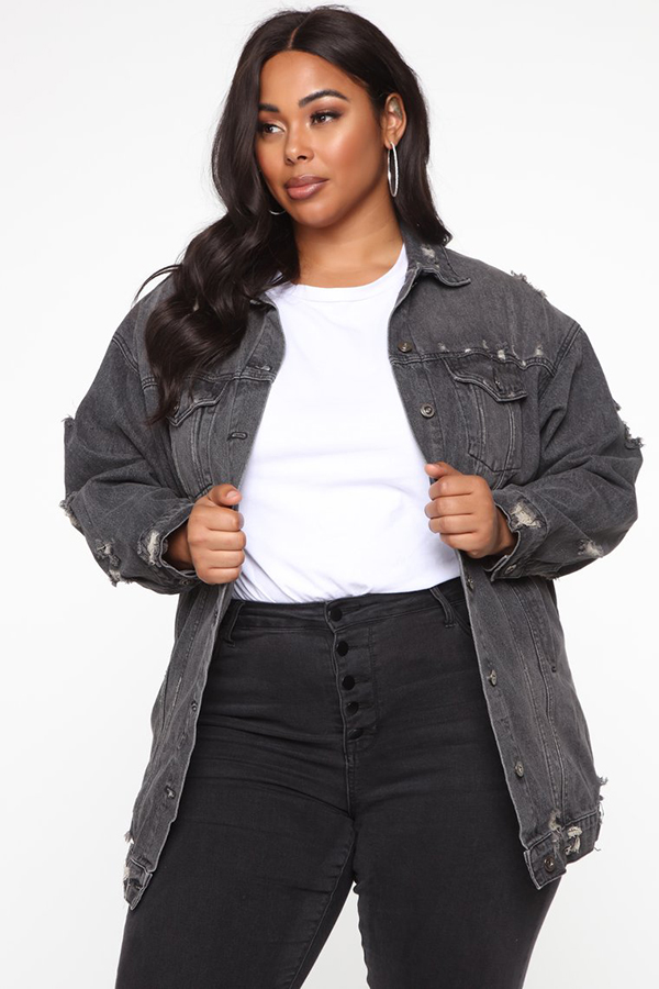 A plus-size model wearing a charcoal denim jacket.