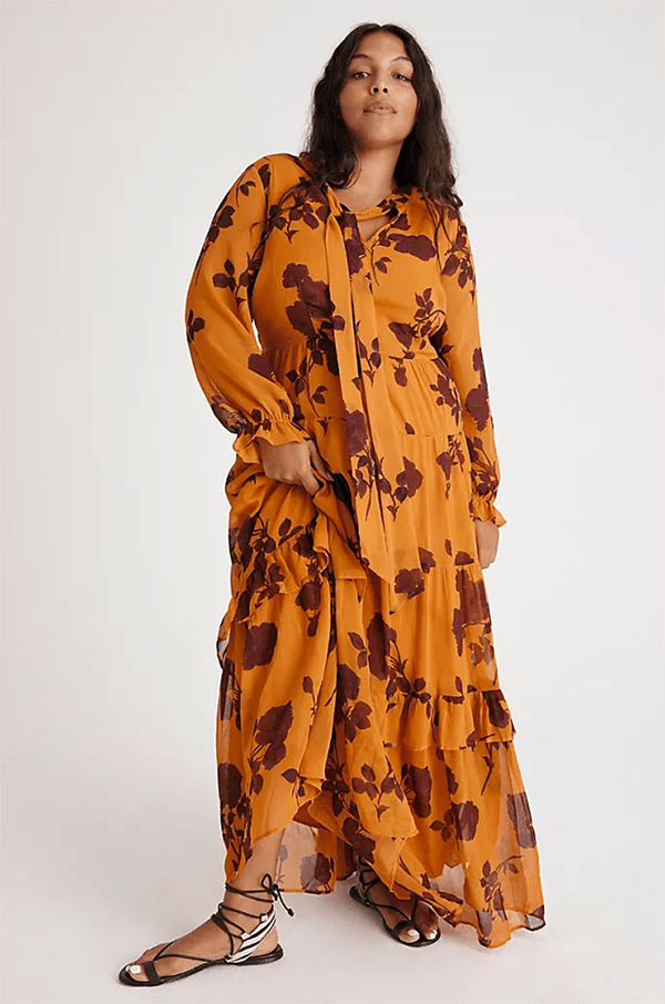A plus-size model wearing a gold and burgundy floral fall maxi dress.