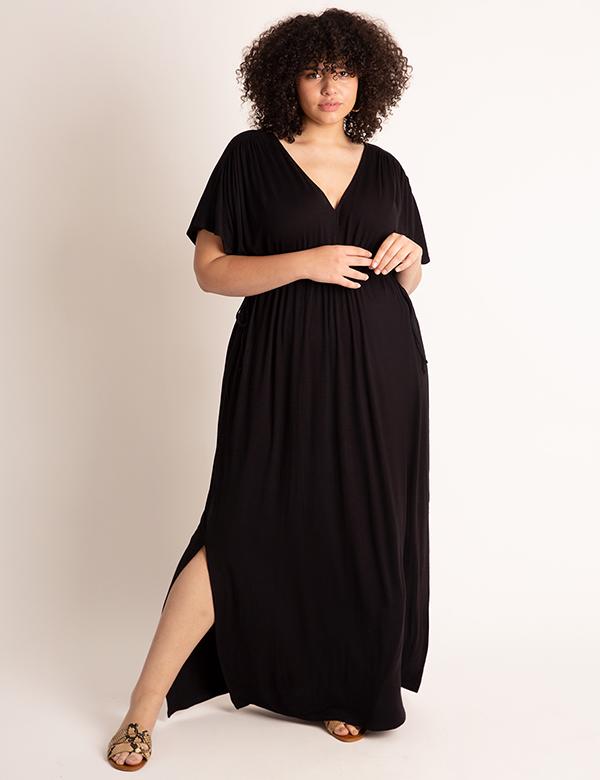A plus-size model wearing a black fall maxi dress.