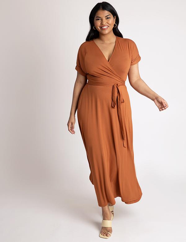 A plus-size model wearing a burnt orange fall maxi dress.