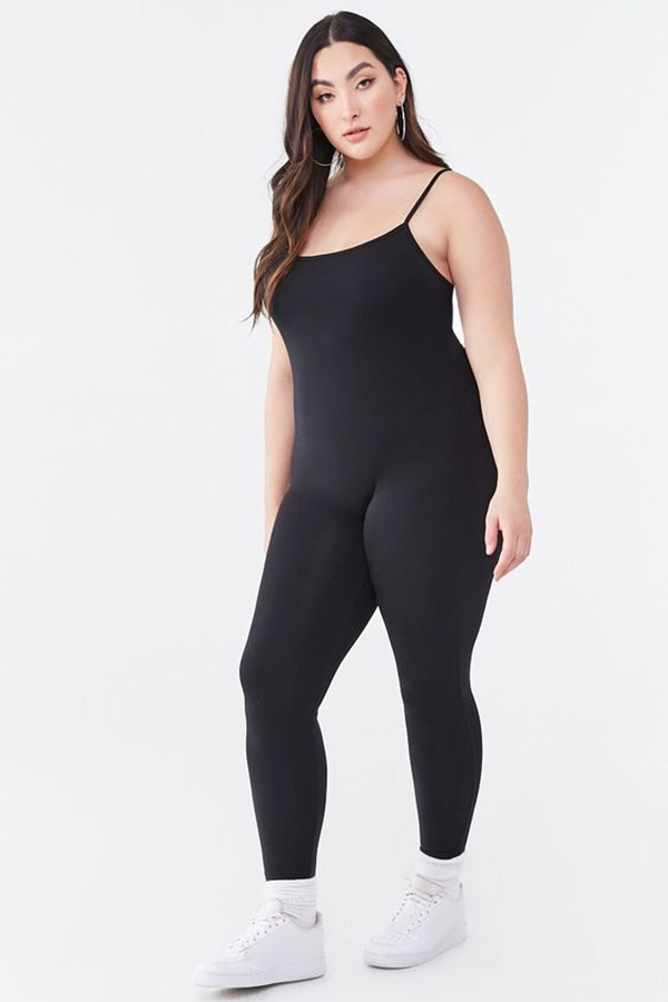 A plus-size model wearing a black lounge jumpsuit.