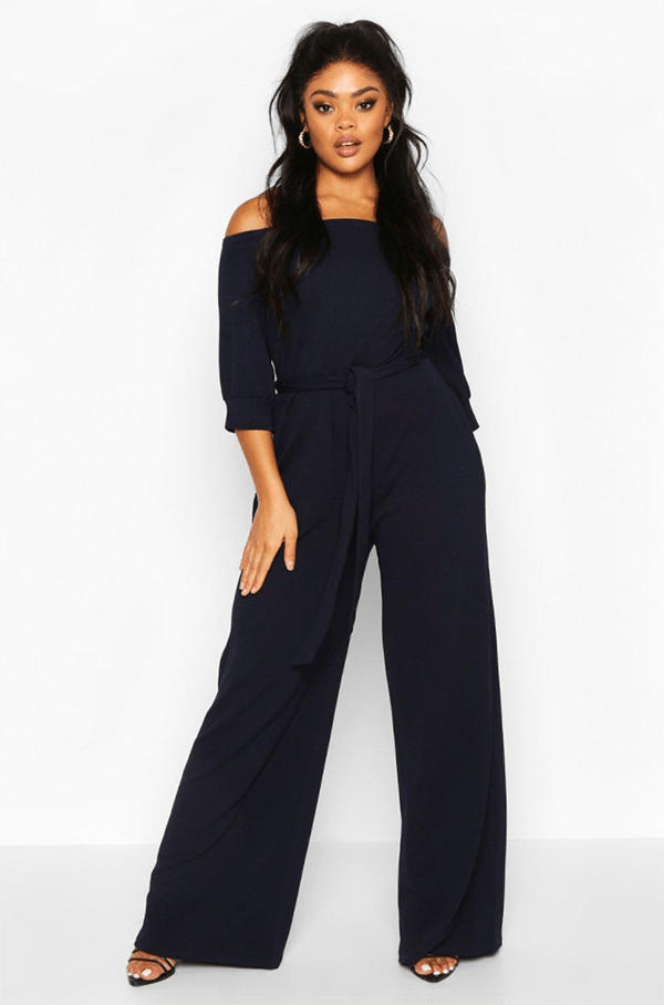 A plus-size model wearing a navy lounge jumpsuit.