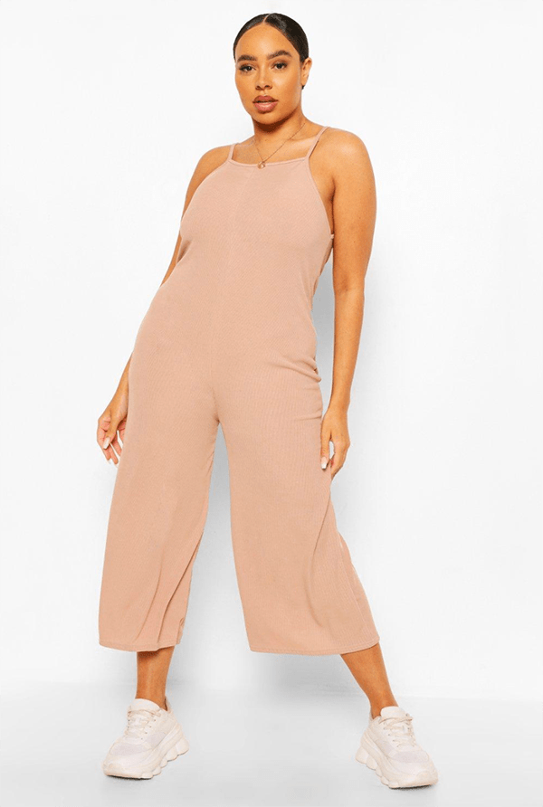 A plus-size model wearing a light pink lounge jumpsuit.