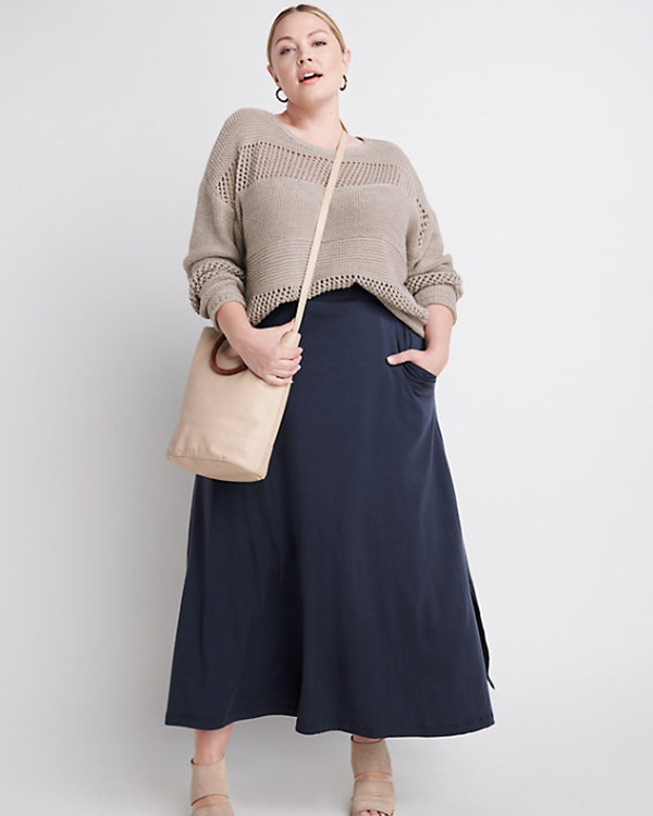 A plus-size model wearing a navy maxi skirt.