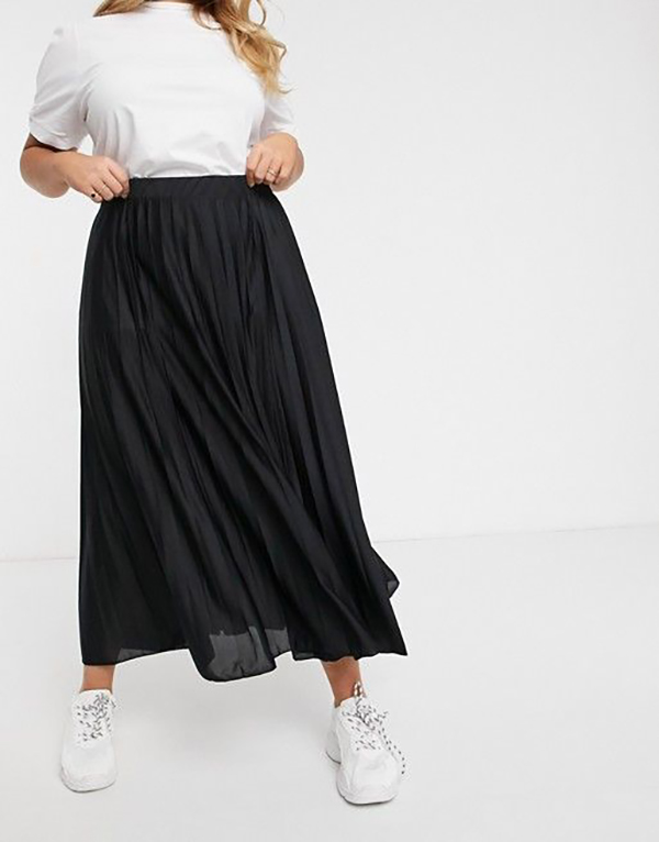 A plus-size model wearing a black pleated maxi skirt.