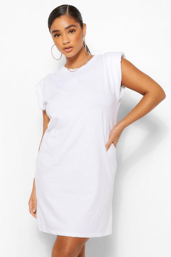 A plus-size model wearing a white shoulder pad T-shirt dress.