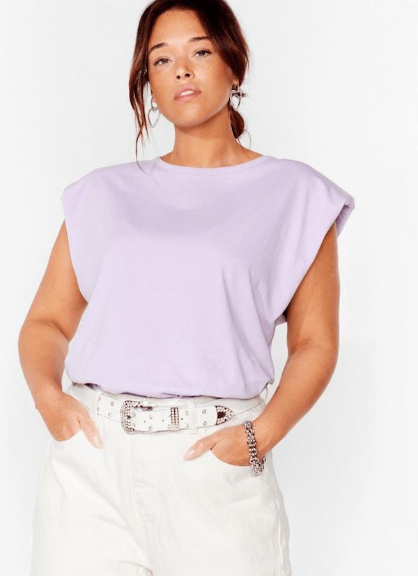 A plus-size model wearing a lavender shoulder pad tank top.