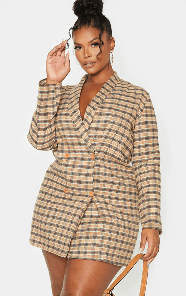 A plus-size model wearing a plaid blazer dress.