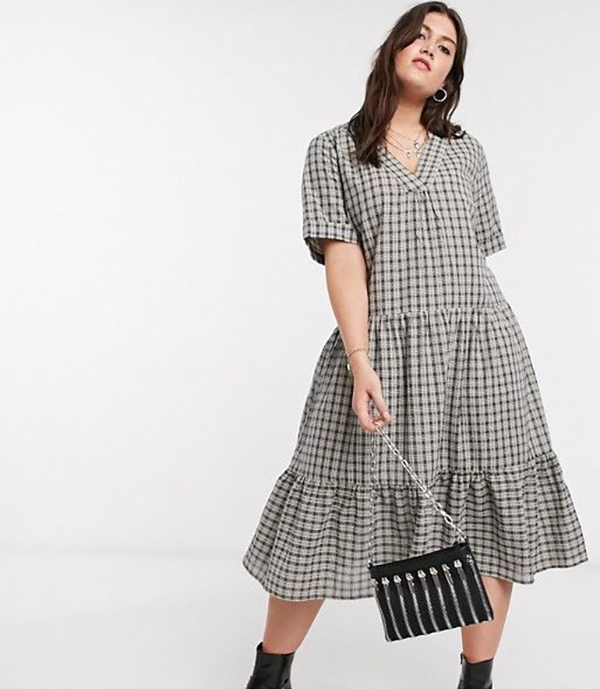 A plus-size model wearing a plaid midi dress.