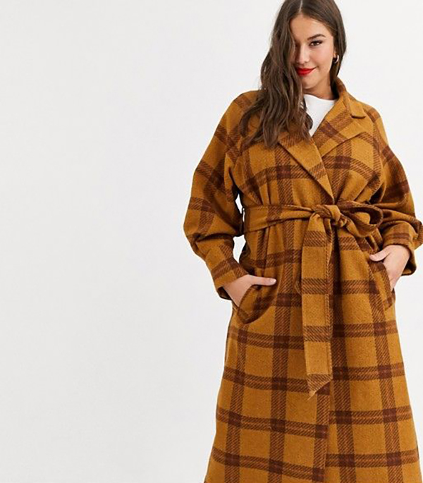 A plus-size model wearing a plaid coat.