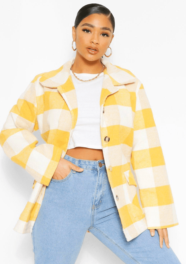 A plus-size model wearing a yellow paid shacket.