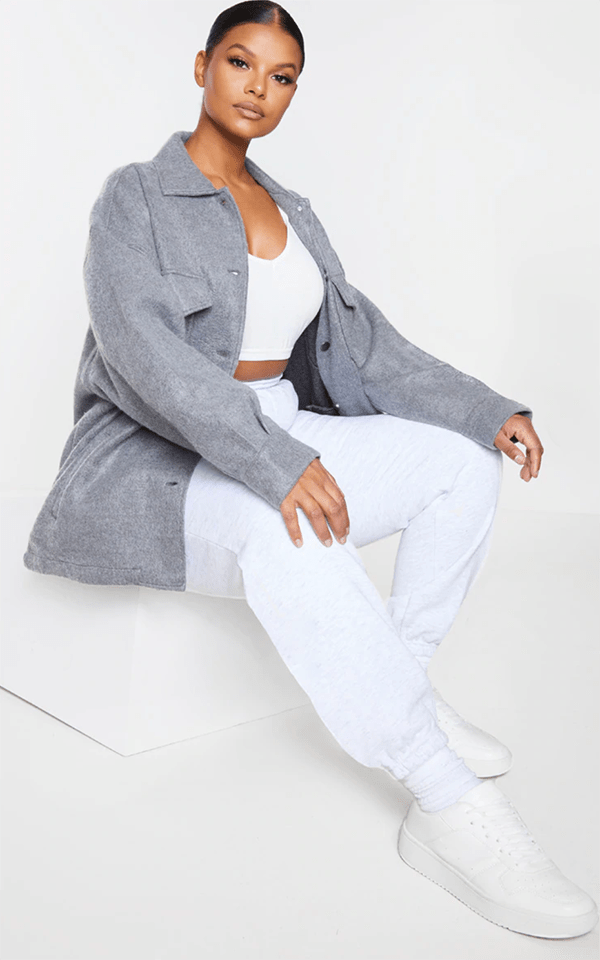 A plus-size model wearing a soft gray shacket.